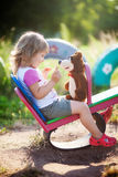 A menina está jogando com um urso do brinquedo Foto de Stock