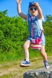 A menina está jogando com uma flor em sua mão, saltando de uma altura, sorrindo imagens de stock royalty free