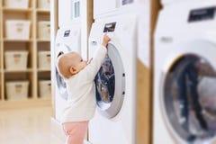 a menina está jogando com uma máquina de lavar foto de stock royalty free