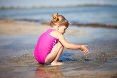A menina está jogando na praia foto de stock
