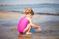 A menina está jogando na praia Fotos de Stock Royalty Free