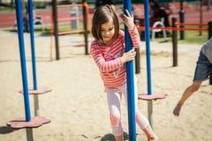 A menina está jogando no campo de jogos no verão Imagem de Stock Royalty Free