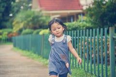 A menina está jogando no jardim Fotos de Stock