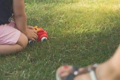 A menina está jogando o carro vermelho no jardim imagens de stock royalty free