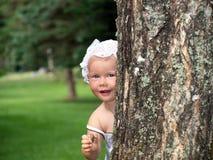 A menina está jogando o hide-and-seek Foto de Stock Royalty Free
