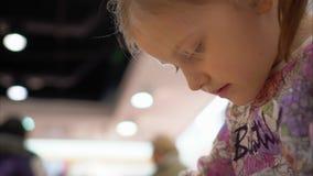 A menina está jogando um jogo usando um smartphone Enfrente o close-up vídeos de arquivo