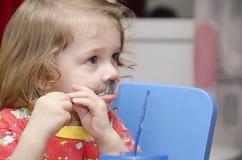 A menina está lambendo a colher, come o bolo, e olha direita Fotografia de Stock Royalty Free
