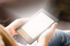 A menina está lendo o ebook no dispositivo digital da tabuleta imagens de stock royalty free