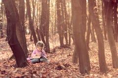 A menina está lendo um livro imagens de stock royalty free