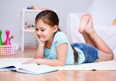 A menina está lendo um livro Imagens de Stock