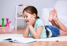 A menina está lendo um livro Imagem de Stock