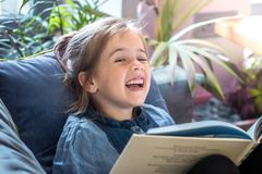 A menina está lendo um livro na sala de visitas no sofá fotos de stock royalty free