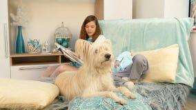 A menina está lendo um livro a seu irmão e a um cão filme
