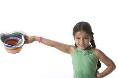 A menina está levantando seu chapéu colorido Fotos de Stock Royalty Free