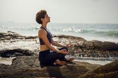 A menina está meditando sobre as rochas Ioga na praia Fotografia de Stock