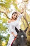 a menina está montando um cavalo Jovem mulher bonita em uma equitação branca do vestido em um cavalo marrom fora fotos de stock royalty free