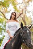 a menina está montando um cavalo Jovem mulher bonita em uma equitação branca do vestido em um cavalo marrom fora imagens de stock royalty free