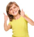 A menina está mostrando o polegar acima do sinal imagens de stock royalty free