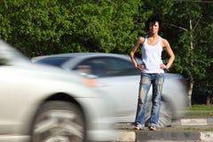 A menina está na estrada entre carros Imagem de Stock Royalty Free