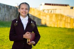 A menina está na roupa da escola com os livros de texto no por do sol e sorri Imagem de Stock Royalty Free