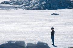 A menina est? no mar congelado e olha ao redor imagens de stock royalty free