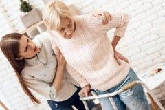 A menina está nutrindo a mulher idosa em casa A mulher está estando com ajuda do caminhante Fere para trás fotografia de stock