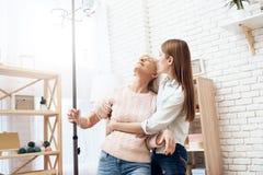 A menina está nutrindo a mulher idosa em casa A mulher está estando com ajuda do polo do contador da gota foto de stock royalty free