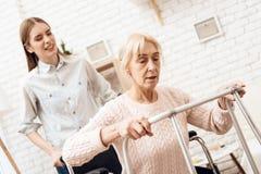 A menina está nutrindo a mulher idosa em casa A mulher está tentando levantar-se da cadeira de rodas fotografia de stock royalty free