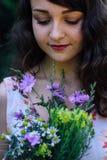 A menina está olhando as flores selvagens Fotografia de Stock Royalty Free