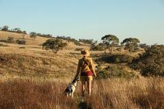 A menina está olhando cangaroos na exploração agrícola australiana com seu cão Fotos de Stock Royalty Free
