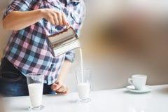 A menina está preparando o café da manhã E a menina derrama o leite em um latte Fotos de Stock Royalty Free