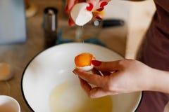 A menina está quebrando o ovo O processo de cozimento Fotografia de Stock
