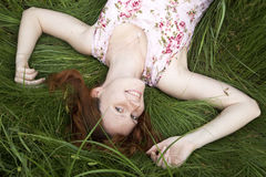 A menina está relaxando na grama Foto de Stock Royalty Free