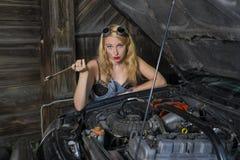 A menina está reparando o carro Fotos de Stock