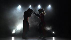 A menina está retrocedendo um indivíduo com seu boxe de treino que kickboxing Luz de atrás Fume o fundo filme