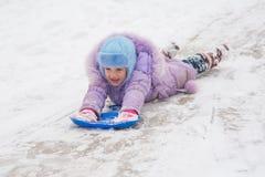 A menina está rolando em seu estômago com headfirst uma neve da corrediça fotografia de stock