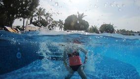 A menina está saltando em uma piscina e está mergulhando sob a água, está comprimindo seu nariz e está fechando os olhos video estoque