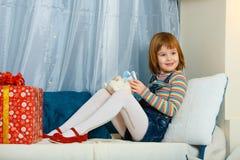 A menina está sentando-se ao lado de um presente fotos de stock