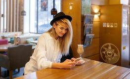A menina está sentando-se em um café e está usando-se um smartphone fotografia de stock royalty free