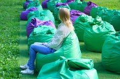 a menina está sentando-se em um saco da cadeira na rua no parque imagem de stock