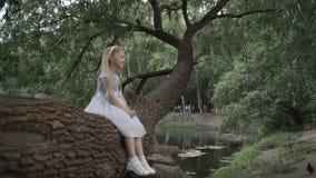 A menina está sentando-se em uma árvore video estoque