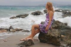 A menina está sentando-se em uma rocha pelo mar Imagem de Stock Royalty Free