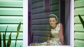 A menina está sentando-se fora da janela e está esperando-se a extremidade da chuva video estoque