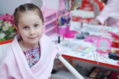 A menina está sentando-se na cadeira do salão de beleza A menina olha contra o espelho e sorri Fundo cor-de-rosa imagens de stock royalty free