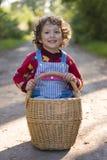 A menina está sentando-se na cesta imagens de stock