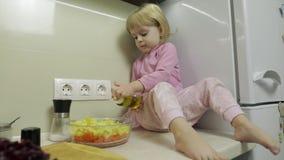 A menina está sentando-se na cozinha e está preparando-se uma salada vídeos de arquivo