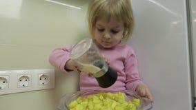 A menina está sentando-se na cozinha e está preparando-se uma salada video estoque