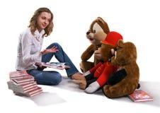 A menina está sentando-se na frente dos brinquedos grandes Imagem de Stock Royalty Free