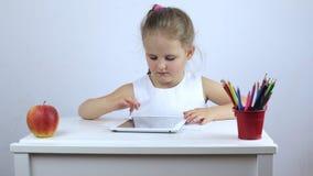 A menina está sentando-se na mesa e é contratada em uma tabuleta video estoque