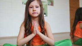 A menina está sentando-se na posição de lótus no fim do gym acima video estoque